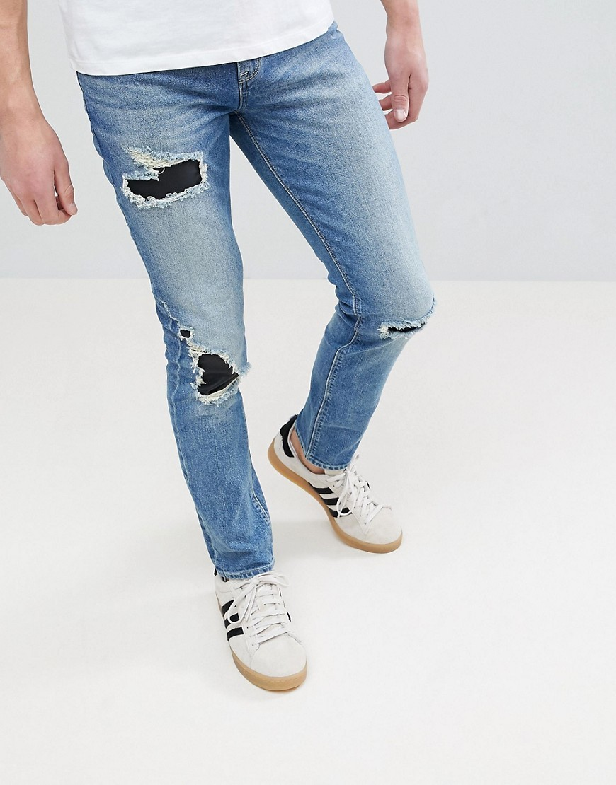 ASOS DESIGN Asos Skinny Jeans In Mid Wash Blue With Rip Repair