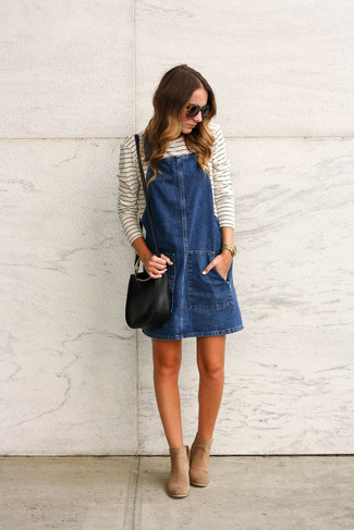 How to wear: black leather crossbody bag, tan suede ankle boots, white and black horizontal striped long sleeve t-shirt, navy denim overall dress