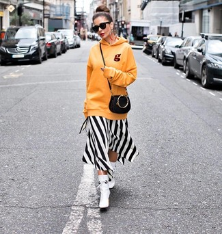How to wear: black leather crossbody bag, white leather ankle boots, white and black vertical striped midi dress, orange hoodie