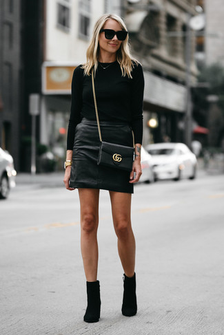 How to wear: black leather crossbody bag, black suede ankle boots, black leather mini skirt, black crew-neck sweater