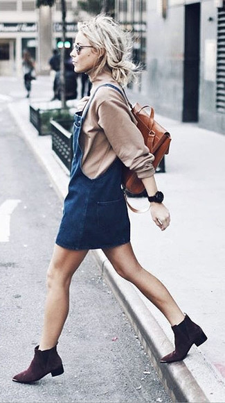 How to wear: tobacco leather backpack, dark brown suede ankle boots, navy denim overall dress, beige turtleneck