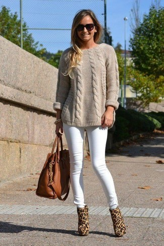How to Wear a Beige Cable Sweater For Women: Choose a beige cable sweater and white skinny jeans for a practical look that's also put together. Take a more refined approach with footwear and add tan leopard calf hair ankle boots to this getup.