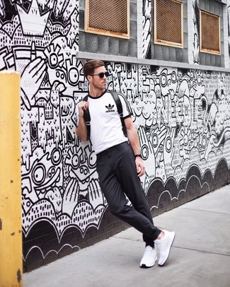 How to wear: black leather backpack, white athletic shoes, charcoal chinos, white and black print crew-neck t-shirt