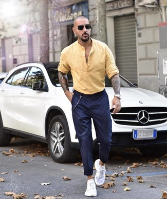 How to wear: black sunglasses, white athletic shoes, navy vertical striped chinos, yellow linen long sleeve shirt