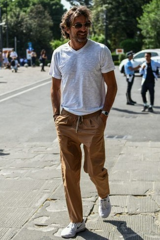 How to Wear Khaki Chinos: This combination of a white v-neck t-shirt and khaki chinos combines comfort and utility and helps keep it low profile yet modern. White athletic shoes are an effective way to punch up this outfit.