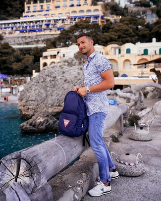 How to wear: navy canvas backpack, white athletic shoes, blue jeans, white and blue print short sleeve shirt