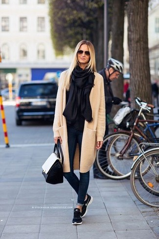 How to wear: black and white leather satchel bag, navy athletic shoes, navy skinny jeans, beige coat