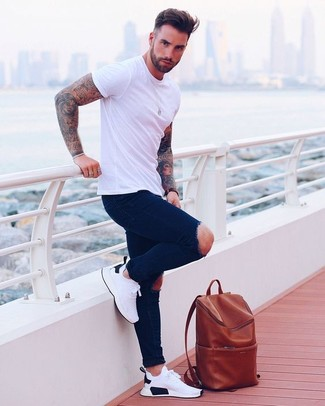 How to wear: tobacco leather backpack, white athletic shoes, navy ripped skinny jeans, white crew-neck t-shirt