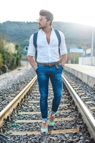 How to wear: navy leather backpack, grey athletic shoes, blue polka dot skinny jeans, white dress shirt