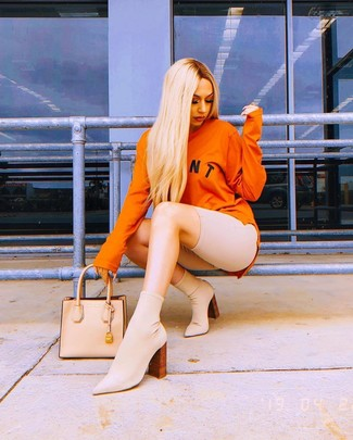 How to wear: beige leather tote bag, beige elastic ankle boots, beige bike shorts, orange print sweatshirt