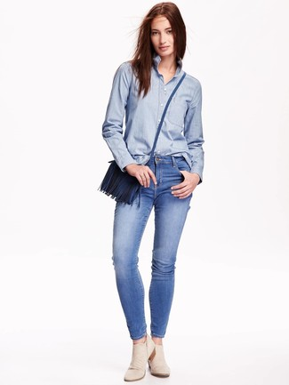 How to wear: blue leather crossbody bag, beige suede ankle boots, blue skinny jeans, light blue chambray dress shirt