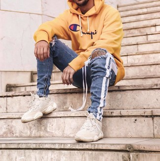 How to wear: beige athletic shoes, blue ripped skinny jeans, yellow print hoodie