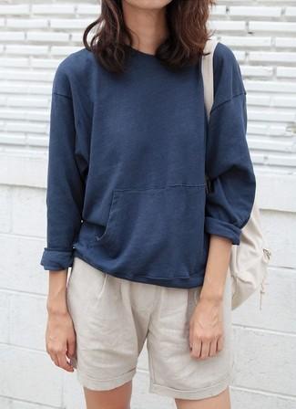 How to wear: beige backpack, beige shorts, navy sweatshirt