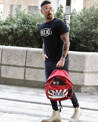 How to wear: red print backpack, beige suede chelsea boots, charcoal skinny jeans, black and white print crew-neck t-shirt