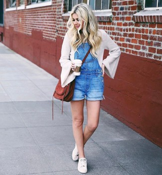 How to wear: beige crew-neck sweater, blue denim overall shorts, white low top sneakers, brown suede crossbody bag