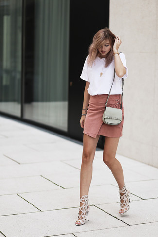 How to Wear a Pink Suede Mini Skirt: We're all seeking practicality when it comes to dressing, and this pairing of a white crew-neck t-shirt and a pink suede mini skirt is a practical illustration of that. Give this outfit an element of polish by slipping into a pair of beige leather heeled sandals.