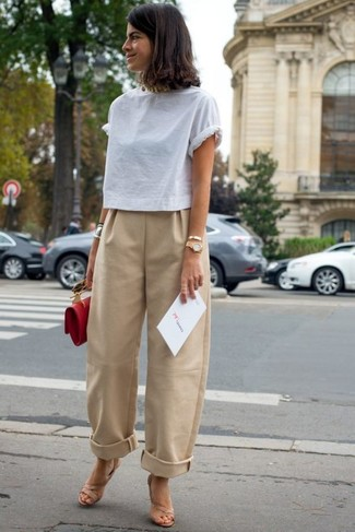 How to wear: red leather clutch, beige leather heeled sandals, tan wide leg pants, white crew-neck t-shirt