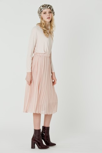 Consider wearing a cream long sleeve t-shirt and a dusty pink pleated midi skirt to create a chic, glamorous look. This outfit is complemented perfectly with oxblood leather ankle boots.