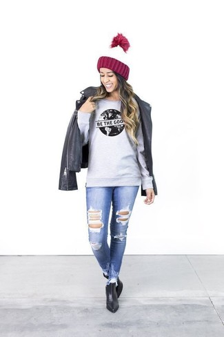 How to wear: black leather biker jacket, grey print sweatshirt, blue ripped skinny jeans, black leather ankle boots