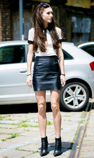 How to wear: burgundy sunglasses, black leather ankle boots, black leather mini skirt, white and black polo