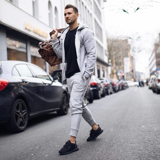 How to wear: brown leather holdall, black athletic shoes, grey track suit, black crew-neck t-shirt