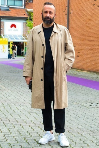 How to Wear a Tan Trenchcoat For Men: This combo of a tan trenchcoat and black chinos is proof that a safe outfit doesn't have to be boring. You can get a bit experimental when it comes to shoes and tone down this getup with white athletic shoes.