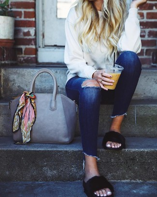 How to wear: grey leather tote bag, black fur flat sandals, navy ripped skinny jeans, white sweatshirt