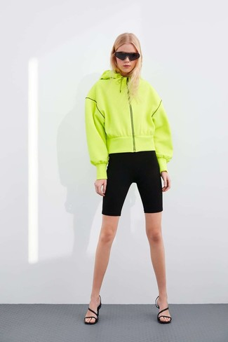 How to wear: black sunglasses, black leather heeled sandals, black bike shorts, green-yellow hoodie