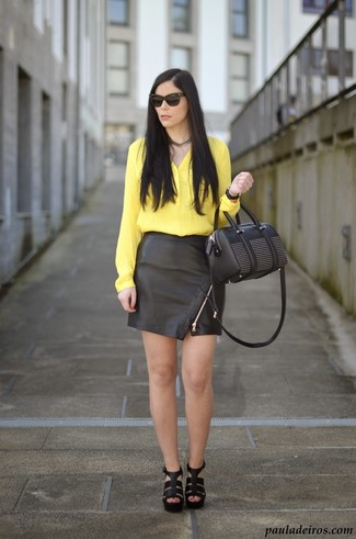 How to wear: black embellished leather handbag, black leather heeled sandals, black leather mini skirt, yellow silk button down blouse