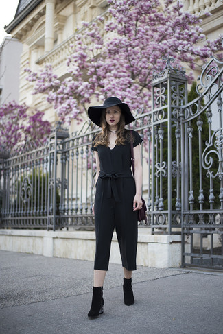How to wear: black jumpsuit, black embellished suede ankle boots, purple suede tote bag, black hat
