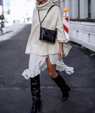 How to Wear Black Leather Knee High Boots: A beige knit oversized sweater and a white and black polka dot wrap dress are the kind of a never-failing casual getup that you need when you have no extra time. Introduce a pair of black leather knee high boots to the mix to instantly change up the ensemble.