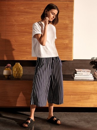 How to wear: black leather flat sandals, black and white vertical striped culottes, white crew-neck t-shirt
