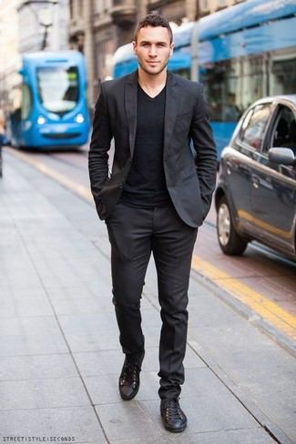 How to Wear Black Leather Low Top Sneakers For Men: The formula for effortlessly classic menswear style? A black suit with a black v-neck t-shirt. Black leather low top sneakers are the most effective way to add a dash of stylish casualness to this outfit.