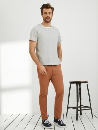 How to Wear Black Leather Low Top Sneakers For Men: A white horizontal striped crew-neck t-shirt and tobacco chinos? It's an easy-to-achieve outfit that you could work on a daily basis. Complement this getup with black leather low top sneakers et voila, this ensemble is complete.