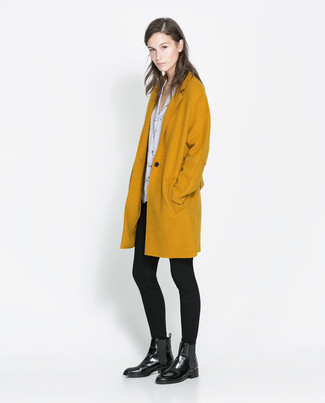 How to wear: black leather chelsea boots, black leggings, white and black print short sleeve blouse, mustard coat