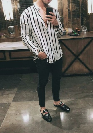 How to wear: black leather watch, black leather low top sneakers, black skinny jeans, white and black vertical striped long sleeve shirt