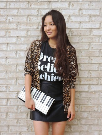 How to wear: white and black print leather clutch, black leather mini skirt, black and white print crew-neck t-shirt, tan leopard open cardigan