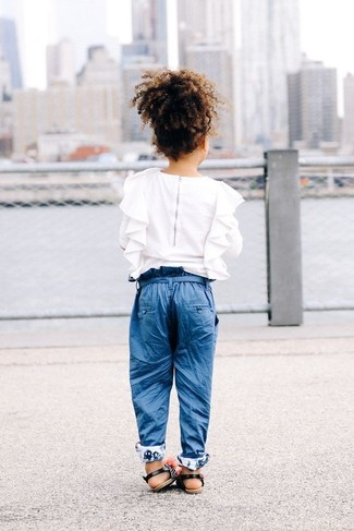 How to Wear a White Ruffle Long Sleeve Shirt For Girls: For an everyday outfit that is full of character and personality suggest that your little angel pair a white ruffle long sleeve shirt with blue trousers. Black sandals are a great choice to complete this look.