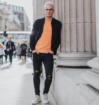 How to wear: grey suede low top sneakers, black ripped skinny jeans, orange crew-neck t-shirt, black bomber jacket