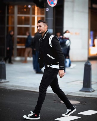 How to wear: black and white canvas low top sneakers, black skinny jeans, white crew-neck t-shirt, black and white varsity jacket