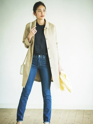 How to Wear a White Leather Crossbody Bag: Showcase that you do off-duty like a fashion pro by opting for a tan trenchcoat and a white leather crossbody bag.