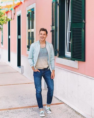 Which Jeans To Wear With a Multi colored Crew-neck T-shirt For Men: A multi colored crew-neck t-shirt and jeans worn together are a perfect match. Dial down the casualness of your look by finishing with a pair of light blue print canvas slip-on sneakers.