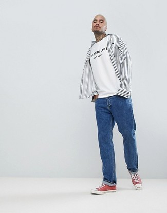 How to wear: red canvas low top sneakers, blue jeans, white and black print crew-neck t-shirt, white and black vertical striped long sleeve shirt