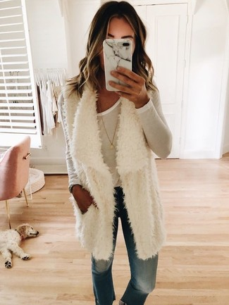 How to wear: gold pendant, blue jeans, white long sleeve t-shirt, white fur vest