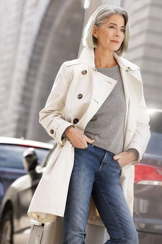 How to wear: blue skinny jeans, grey crew-neck sweater, beige trenchcoat