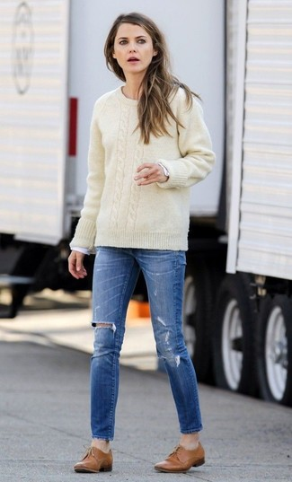 How to Wear a Beige Cable Sweater For Women: This relaxed combination of a beige cable sweater and blue ripped skinny jeans is extremely easy to throw together in no time flat, helping you look amazing and prepared for anything without spending too much time combing through your wardrobe. If you want to immediately up the style ante of this ensemble with footwear, why not complement this ensemble with a pair of tan leather oxford shoes?