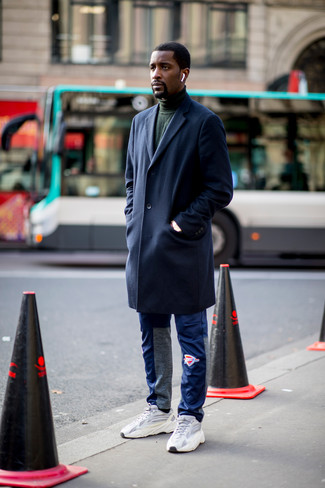 How to wear: grey athletic shoes, blue sweatpants, dark green turtleneck, navy overcoat