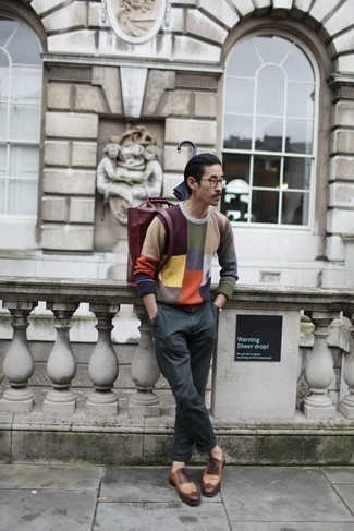 How to Wear a Burgundy Leather Backpack For Men: If you prefer comfort dressing, why not take this combination of a multi colored crew-neck sweater and a burgundy leather backpack for a spin? You can get a little creative on the shoe front and complement your outfit with a pair of brown leather brogues.