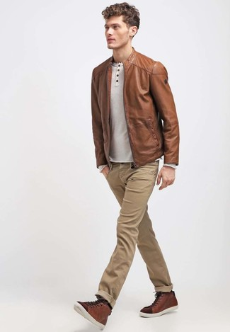 How to wear: brown leather bomber jacket, beige long sleeve henley shirt, khaki jeans, brown leather high top sneakers