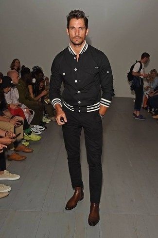How to Wear a Black Varsity Jacket For Men: A black varsity jacket looks especially nice when matched with black chinos in a laid-back getup. You can get a bit experimental on the shoe front and spruce up this look with a pair of brown leather chelsea boots.